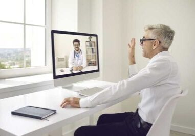 Physician consulting with ENT office management specialist via video conference.