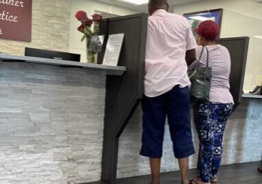 Couple at reception desk of a medical office.