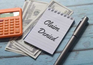 """calculator, American cash money, a notepad with the words """"claim denied"""" and a pen"""