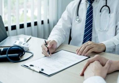 Doctor writing notes for patient file to be used for billing and coding.