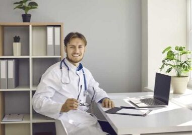 Happy male doctor working in his medical office in hospital. Portrait of handsome young man in white lab coat sitting at desk with laptop computer, holding glasses, looking at camera and smiling